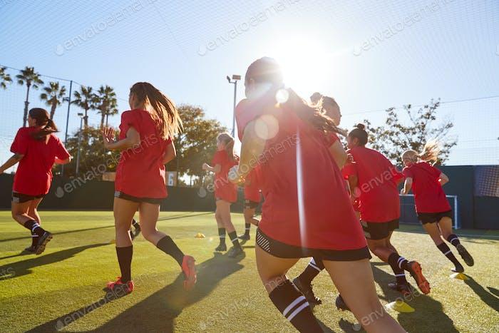 Womens Football Team Run während der Ausbildung für Fußballspiel auf Astro-Rasen Platz