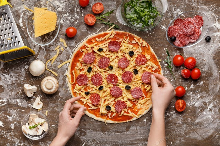 Woman preparing pizza, decorating it with salami