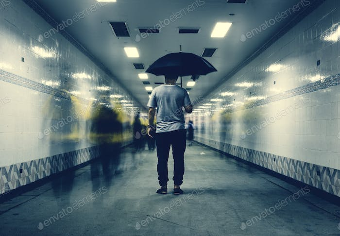 Rear view of a man holding umbrella with blurred people long exposure technique
