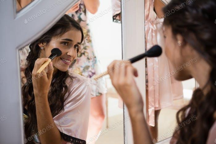 Bride applying her makeup doing her wedding preparation
