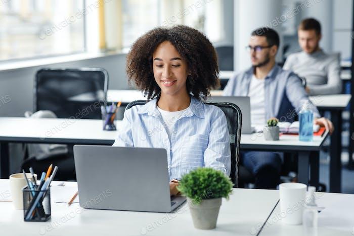 Employee works in coworking office during coronavirus. Smiling african american millennial woman
