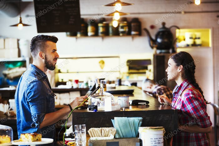 Specialist coffee shop. A man behind the counter using a touch screen to record transactions, and a