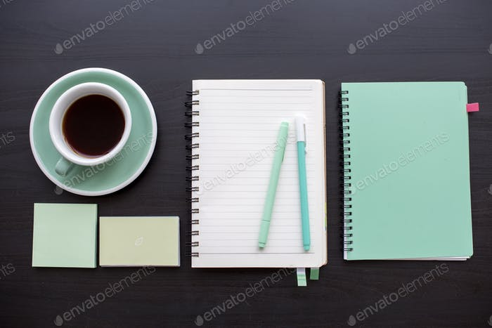 Open notebook with sticky note and pens stationery on dark gray