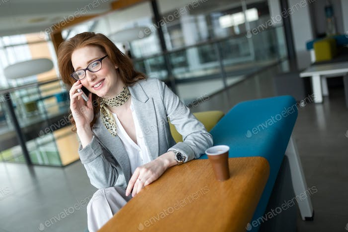 Business woman with coffe and talking on the phone in office