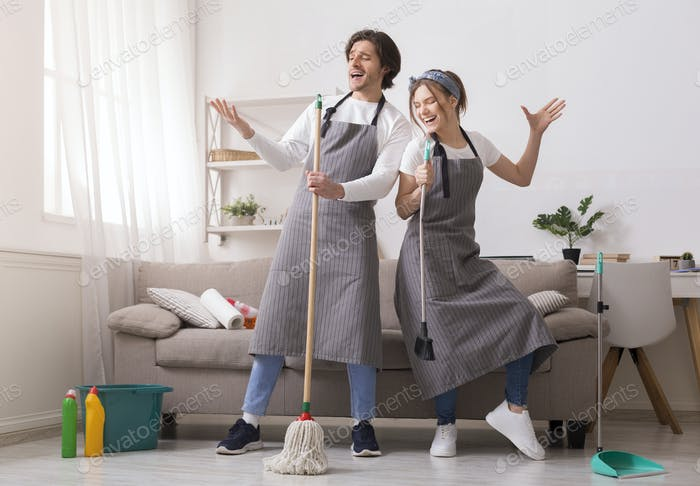 Couple Having Fun While Cleaning Home, Playing With Mop And Broom