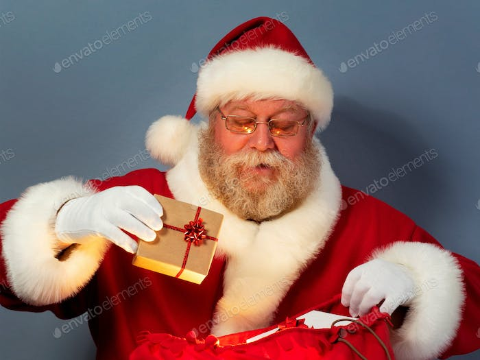 Santa Claus putting gifts into his sack