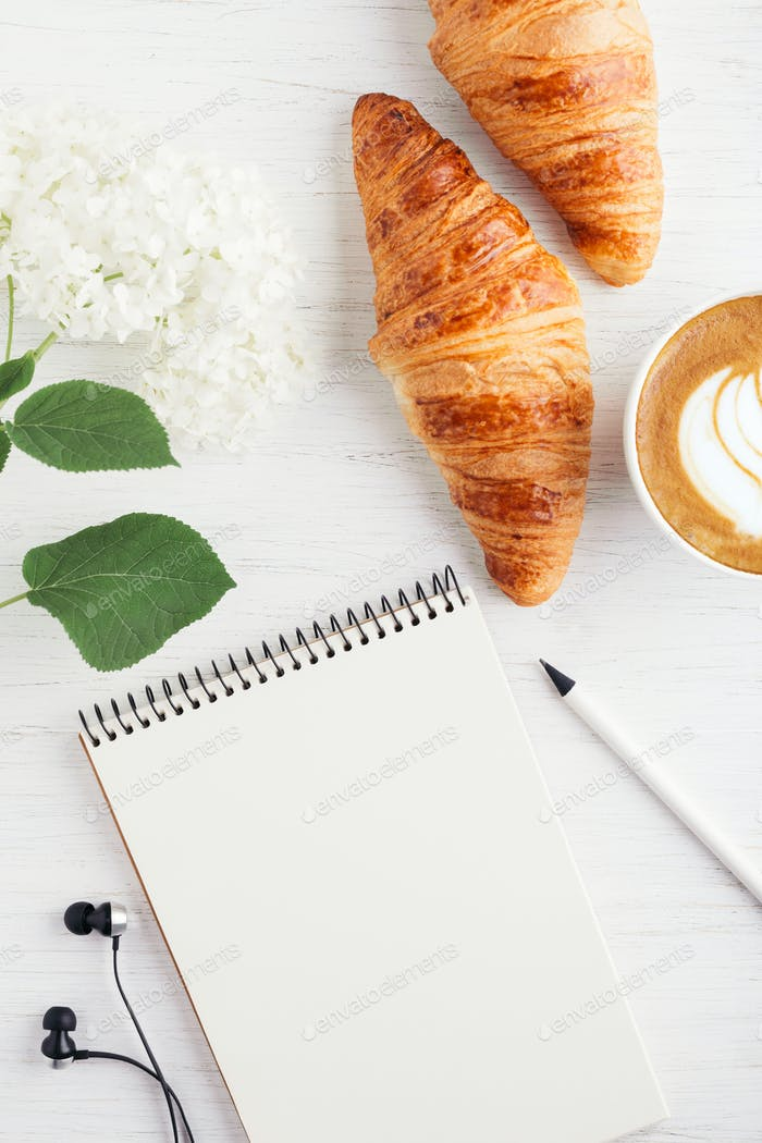 Croissants, Cup of Cappuccino and Notebook.