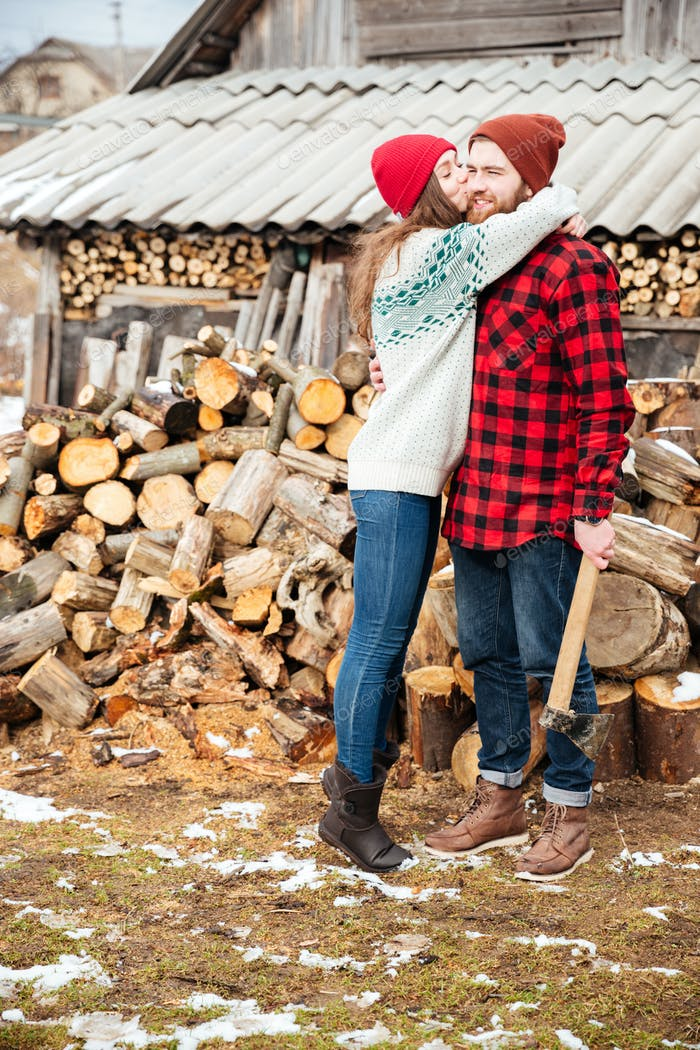 Happy woman hugging handsome man with axe in village