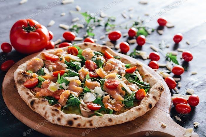 Pizza mit Lachs, Tomaten, Rucola und Parmesan