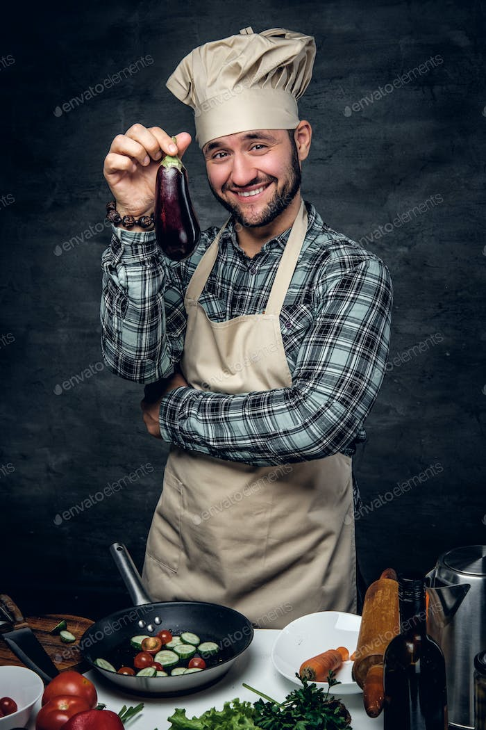 Smiling cook male holds eggplant.