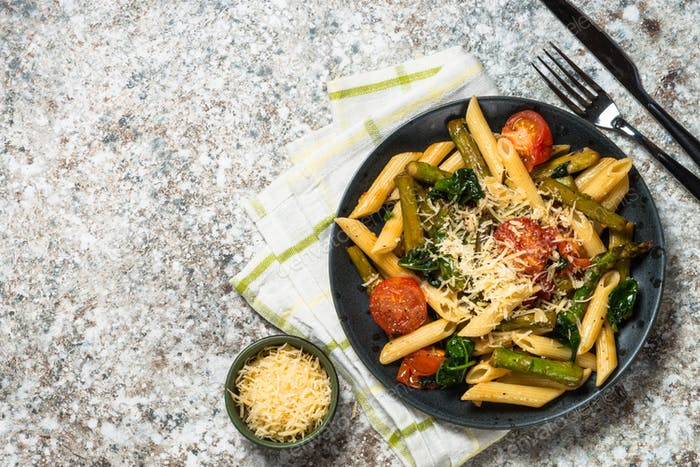 Vegan pasta penne with spinach, asparagus and tomato