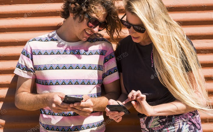Millennial young people couple together using both cellular mobile phone looking the devices