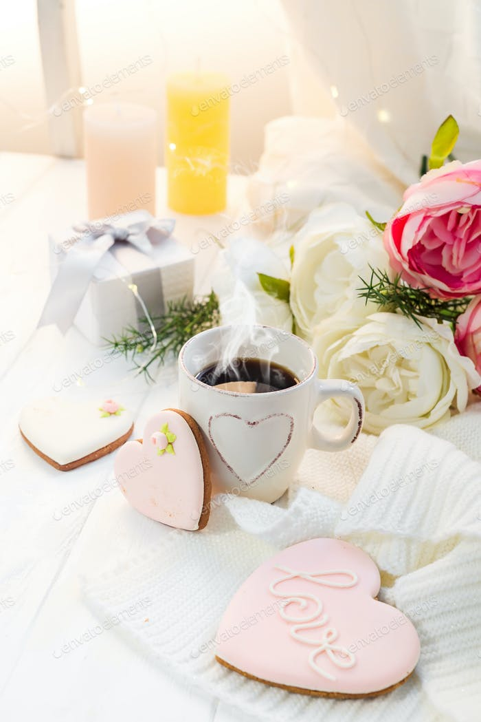 Heart cookies with cup of coffee on wooden background with plaid, copy space
