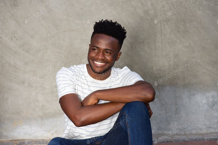 Thumbnail for handsome smiling african man sitting by wall