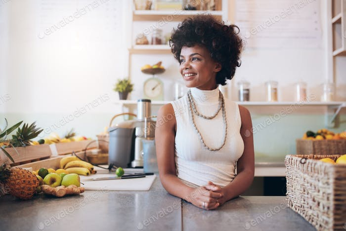 Schöne junge Frau arbeitet an Saftbar