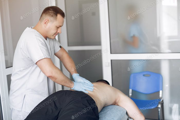 The doctor massages the man in the hospital
