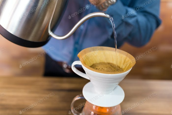 Barista pouring water on coffee with filter in coffee shop