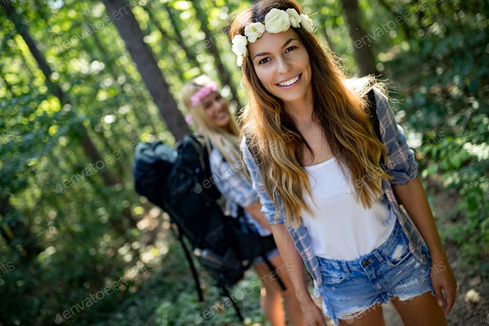 Hiker women friends with backpack walking on path in summer forest