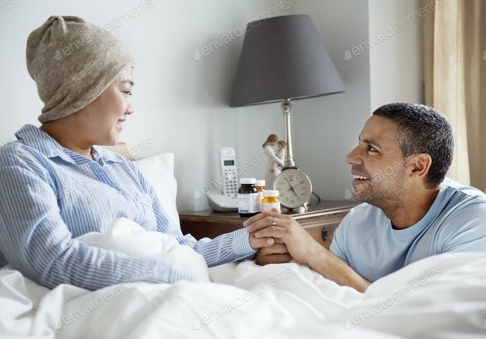 A sick woman in bed with her partner