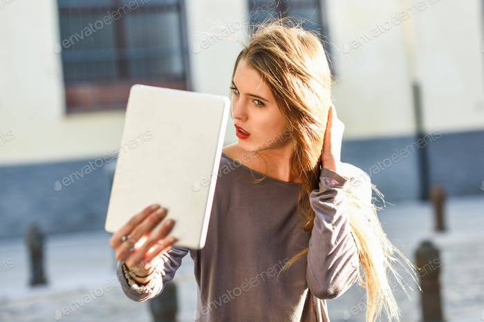 Young woman selflooking at tablet
