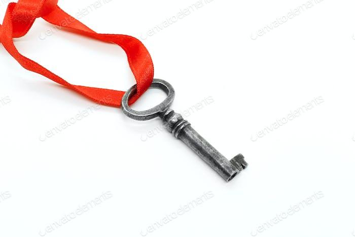 Vintage Silber Schlüssel mit rotem Band auf weißem Hintergrund