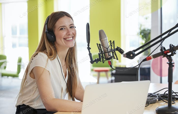 Young woman broadcasting in a studio smiling to camera