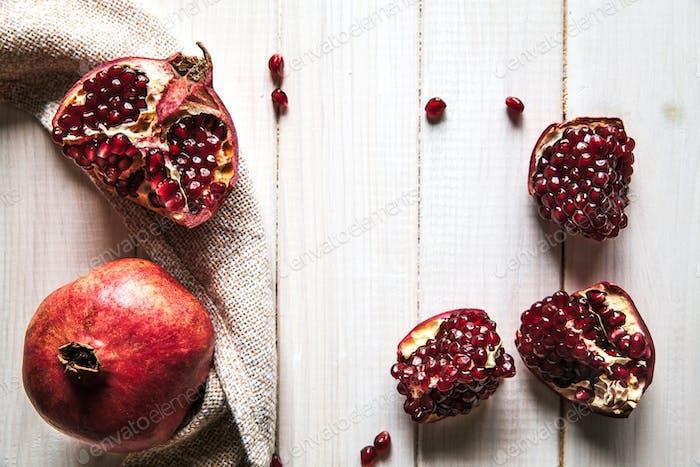 Reife Granatäpfel, Serviette und Tafelmesser auf Holzuntergrund