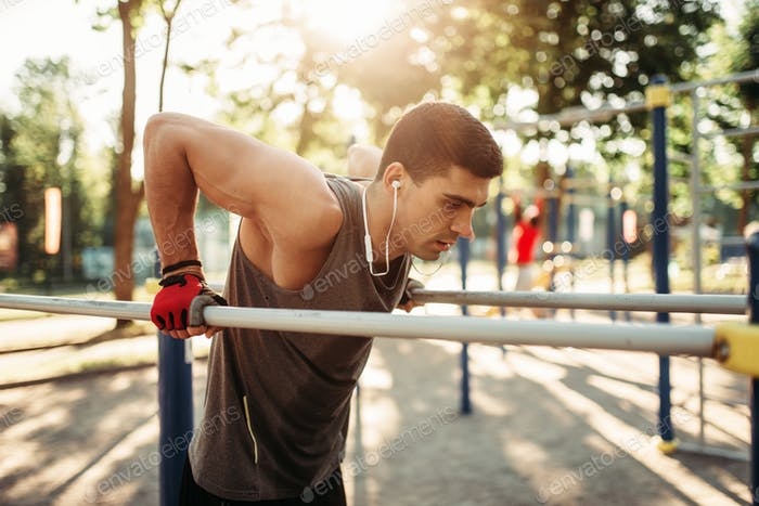 Male athlete exercises on parallel bars outdoor