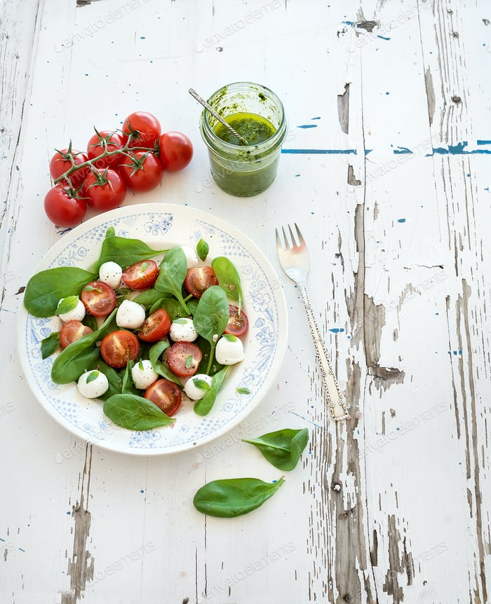Caprese salad, homemade pesto sauce. Cherry-tomatoes, baby spinach and mozzarella in ceramic plate