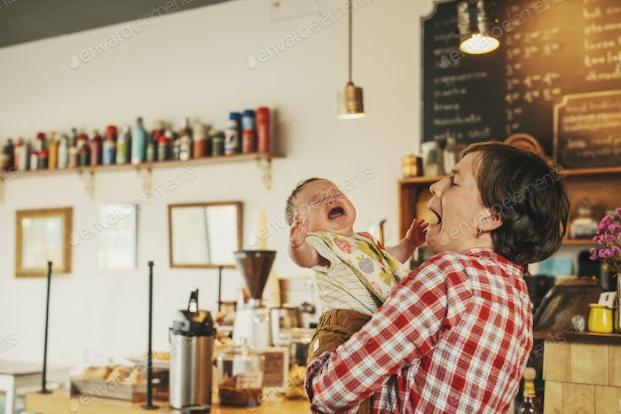 A woman holding a crying baby in a coffee shop.