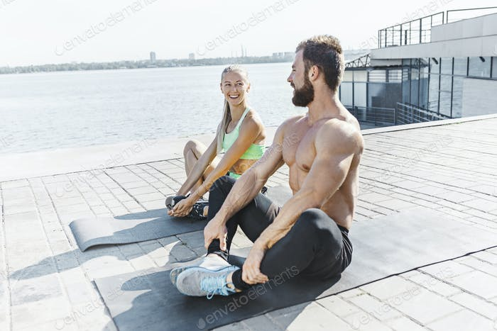 Fit fitness woman and man doing stretching exercises outdoors at city