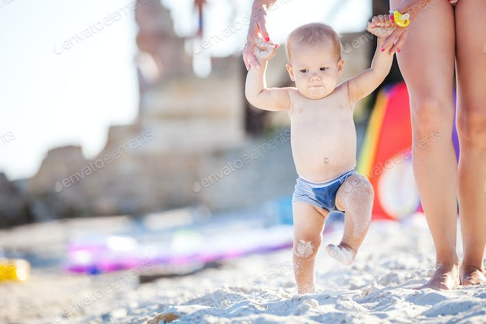Baby boy walking along beach with mom's suppor