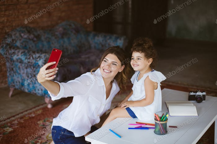 Young cheerful mother and cute little daughter happily taking ph