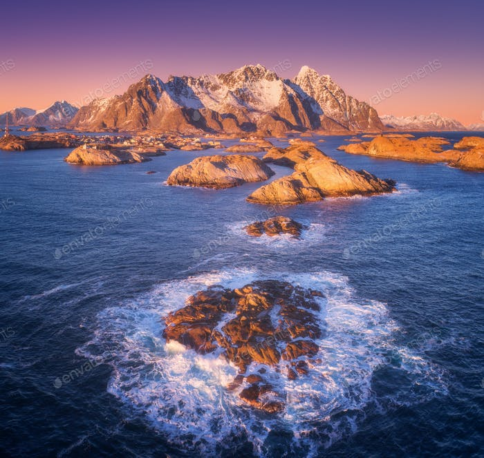 Aerial view of rocks in sea waves, Henningsvaer city, mountains
