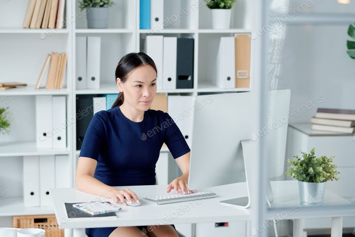 Young brunette designer looking at computer screen while concentrating on work