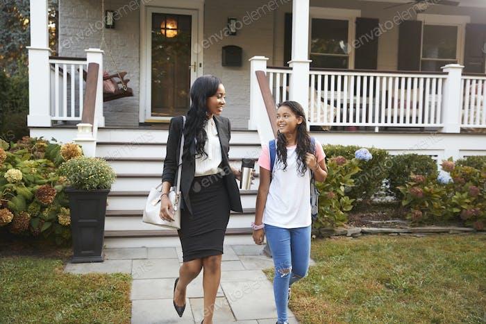 Businesswoman Mother Walking Daughter To School On Way To Work