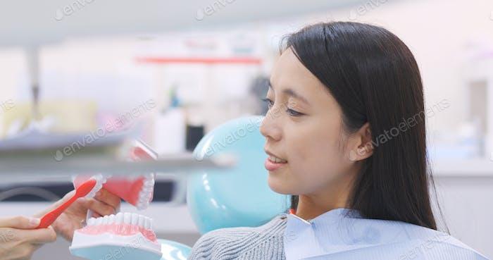 Dentist teaching patient how to brush teeth