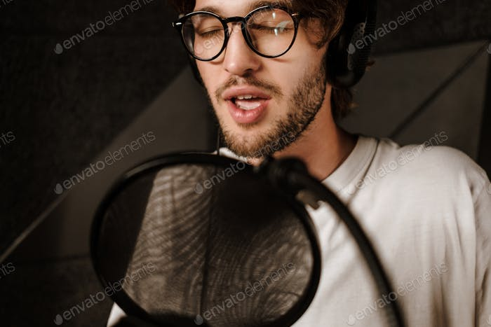 Handsome musician guy in headphones sensually singing in microphone in sound recording studio