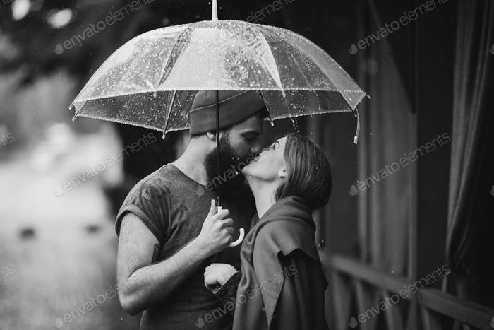 guy and the girl kissing under an umbrella