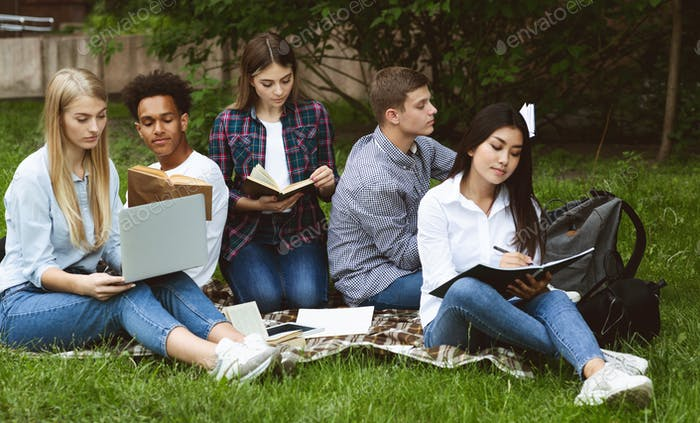 Group of students studying in college campus, preparing for classes