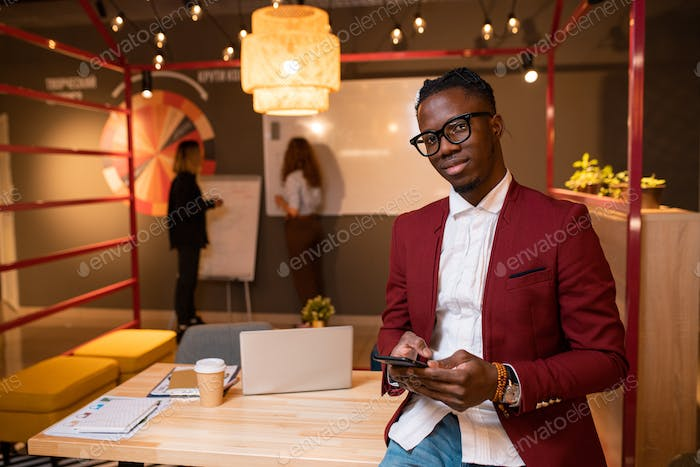 Young African businessman with mobile phone standing by table in front of camera