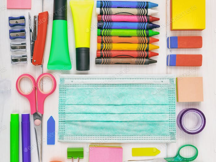 Surgical mask and school supplies background. Coronavirus spread prevention measure