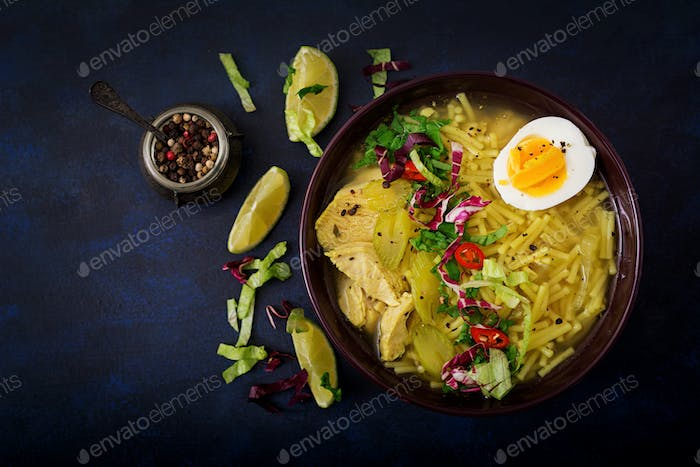 Noodle soup with chicken, celery and egg in a bowl on a black background. Flat lay. Top view.