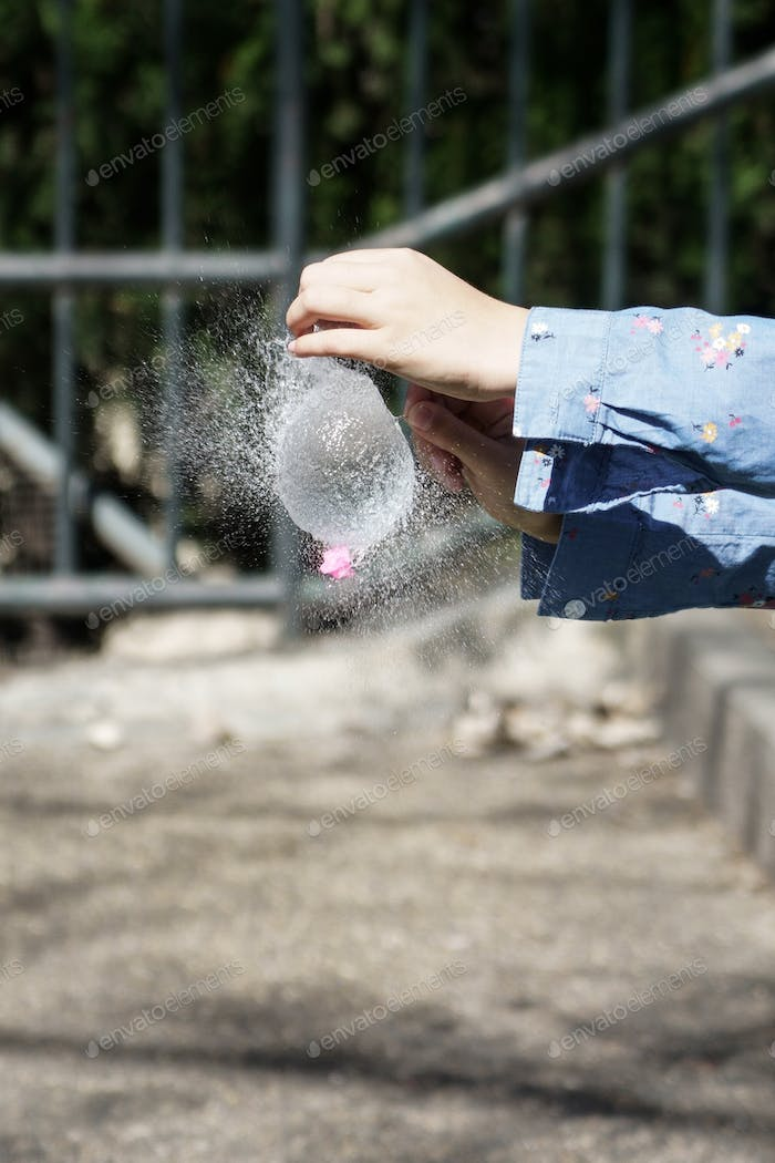 Girl's hands blowing up a water balloon with a needle