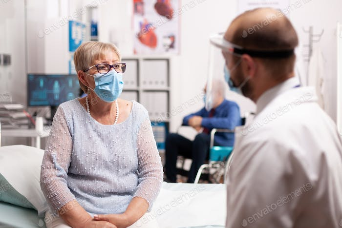 Worried senior woman with face mask looking at doctor