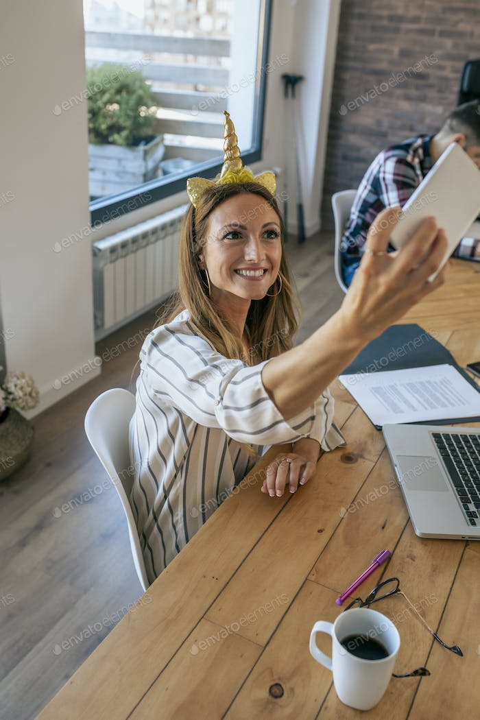 Businesswoman taking selfie with unicorn headband