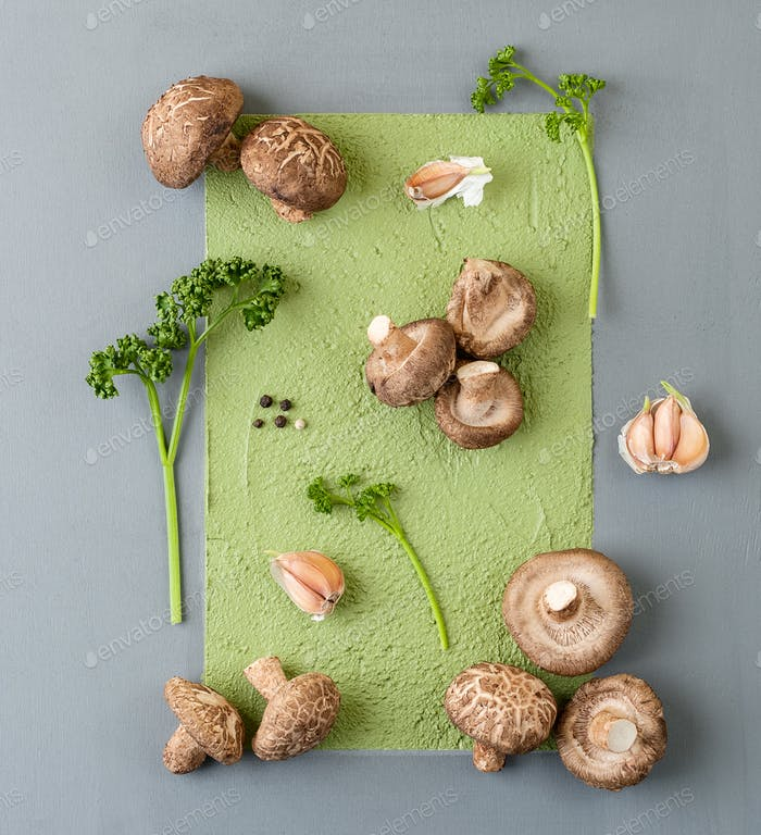 Fresh shiitake mushrooms, parsley and garlic on an abstract gray