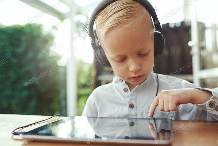 Pequeño chico pensativo seleccionando una Novedad banda sonora
