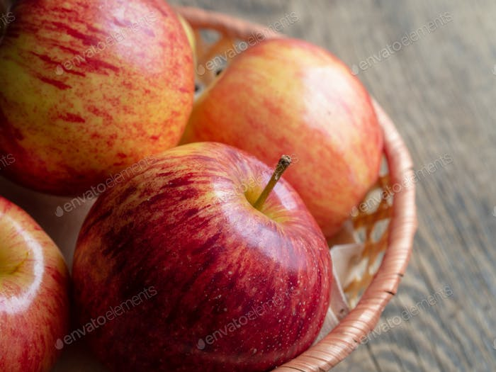ripe juicy red apples in a basket on a wooden table, close up