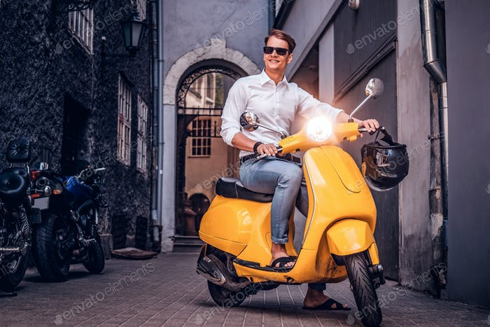 Handsome man riding on vintage Italian scooter in the old narrow street of Europe
